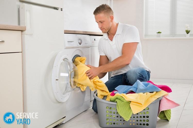 Žmogus, nešiojantis nešvarius drabužius, į skalbimo mašiną