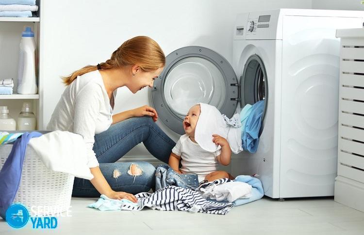 motina namų šeimininkė su kūdikiu, užsiimanti skalbiniais, į skalbimo mašiną sudeda drabužius