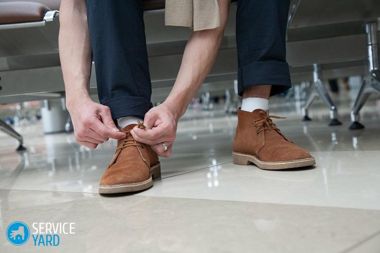 Homme à l'aéroport laçant ses chaussures en daim