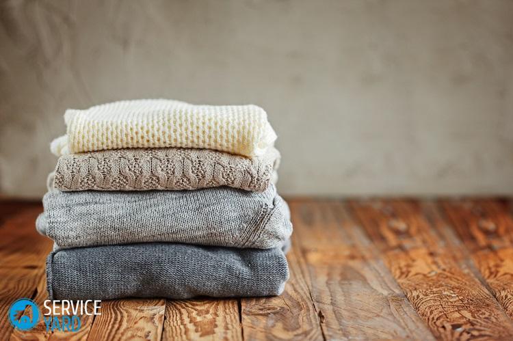 Pile de vêtements d'hiver tricotés sur fond en bois, chandails, espace